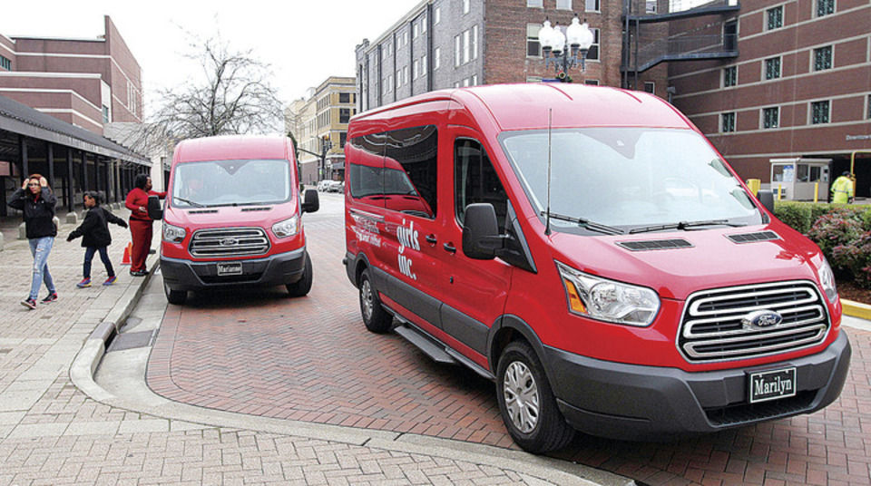 Two of the four new Girls Incorporated transit vans park in front of the RiverPark Center on December 22 as children from the organization unload to take a tour of the facility. The vans were purchased with grants from Impact 100 and the Marilyn and William Young Foundation and replace older, aging club vehicles. Photo by Greg Eans
